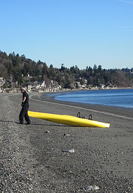 man with canoe on beach